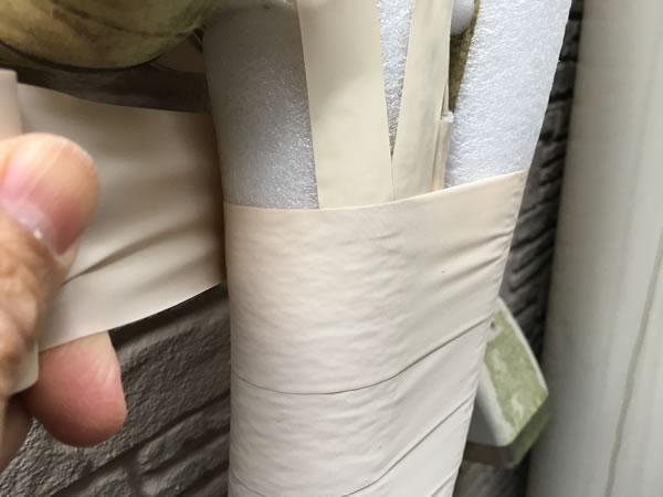 断熱パイプカバーに保護テープを巻いていく